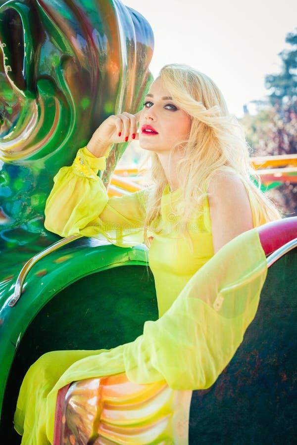 Belle jeune femme blonde dans la longue journée d'été de portrait de mode de robe élégante extérieure en parc d'attractions de vi photographie stock