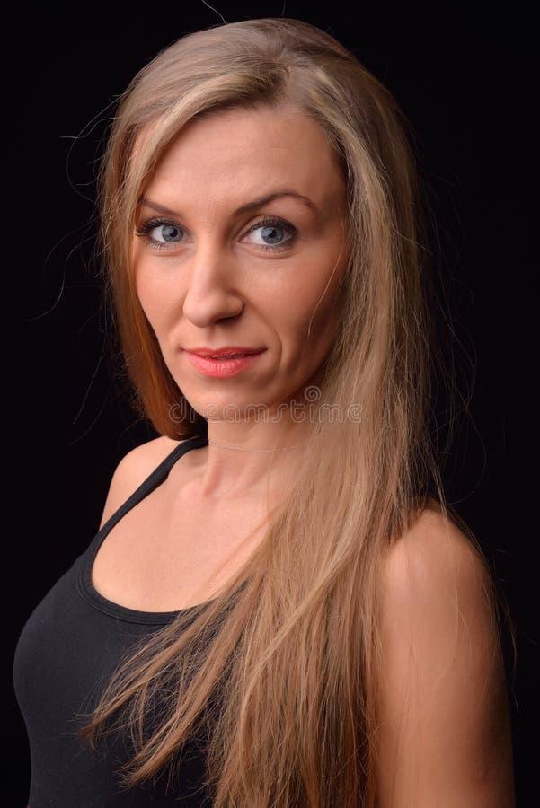 Belle jeune femme blonde dans un tricot noir posant dans un s photographie stock libre de droits