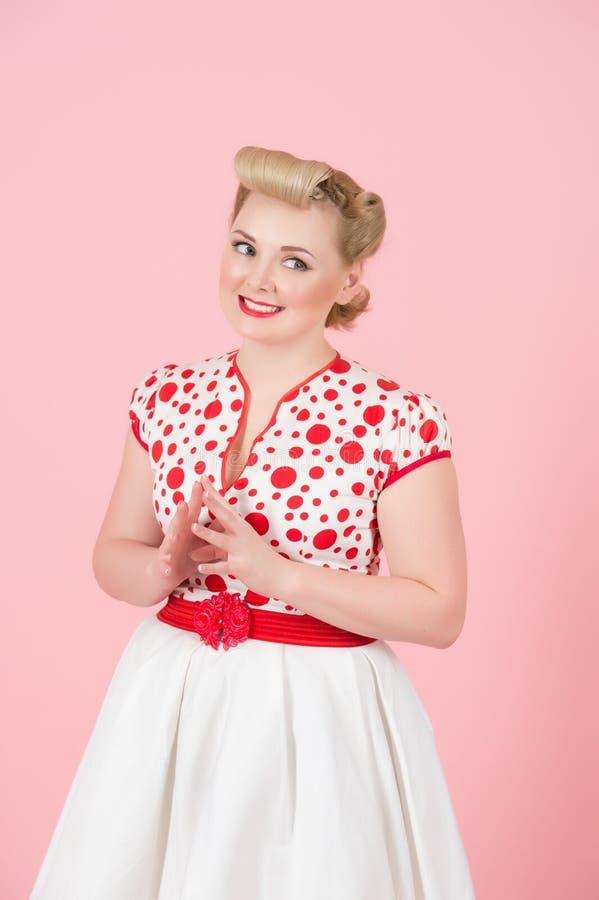 Belle jeune femme blonde de boucle tenant des doigts sur le coffre regardant à gauche et le sourire toothy photo stock