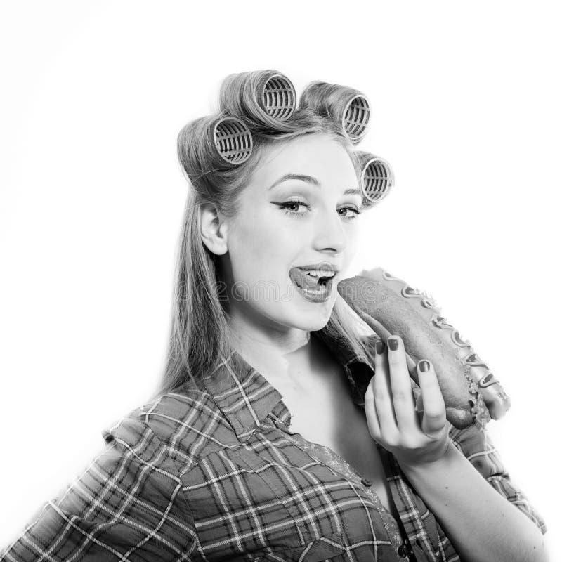 Belle jeune femme blonde de pin-up dans des bigoudis photo stock
