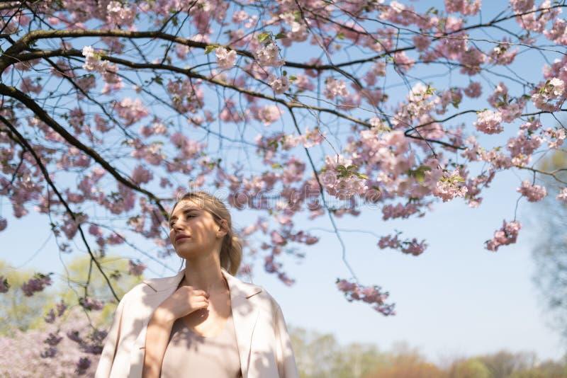 Belle jeune femme blonde en parc de Sakura Cherry Blossom au printemps appr?ciant la nature et le temps libre pendant elle voyage image stock