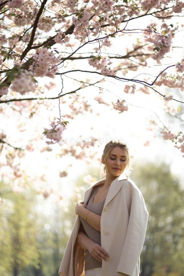 Belle jeune femme blonde en parc de Sakura Cherry Blossom au printemps appr?ciant la nature et le temps libre pendant elle voyage photographie stock