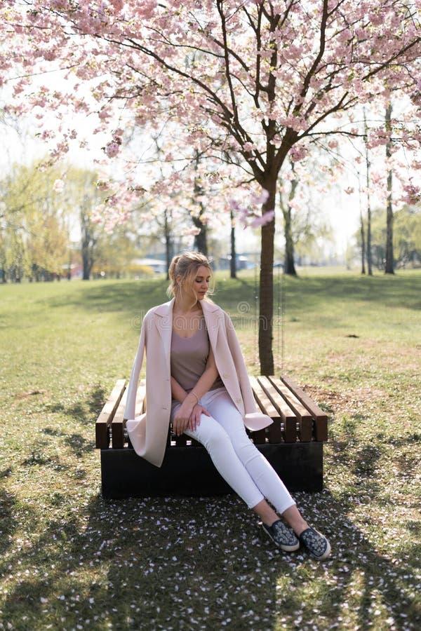 Belle jeune femme blonde en parc de Sakura Cherry Blossom au printemps appr?ciant la nature et le temps libre pendant elle voyage photographie stock libre de droits