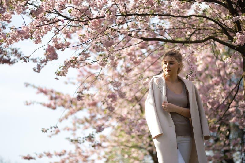 Belle jeune femme blonde en parc de Sakura Cherry Blossom au printemps appr?ciant la nature et le temps libre pendant elle voyage photos libres de droits