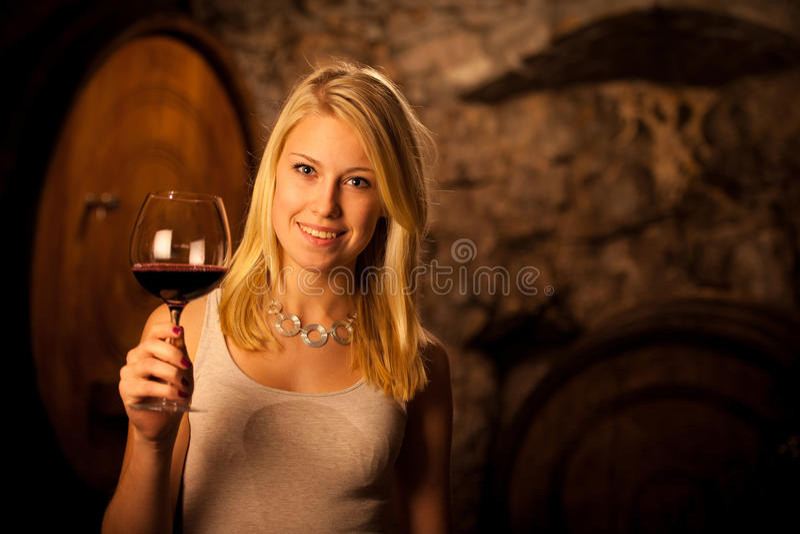 Belle jeune femme blonde goûtant le vin rouge dans une cave photos stock
