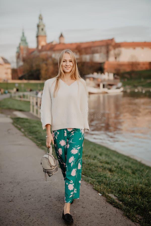 Belle jeune femme blonde marchant près de la rivière au coucher du soleil Ses cheveux soufflant dans le vent images stock