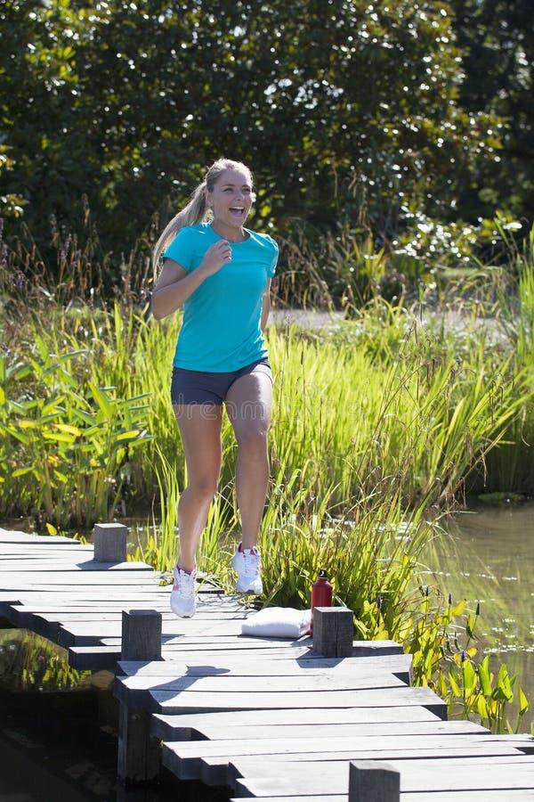 Belle jeune femme blonde riante courant et sautant pour l'amusement photo stock