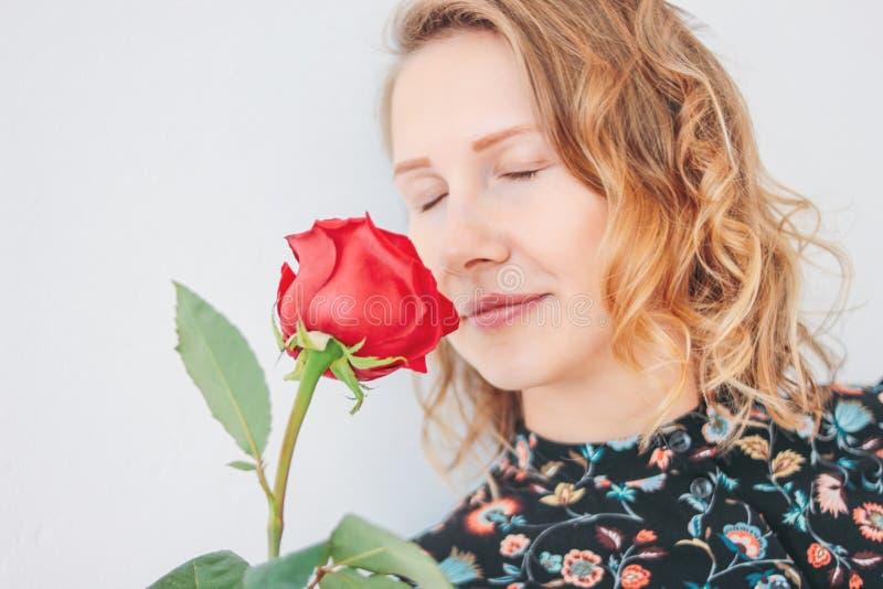 Belle jeune femme blonde romantique dans la robe avec la rose rouge sur le fond blanc d'isolement photographie stock libre de droits