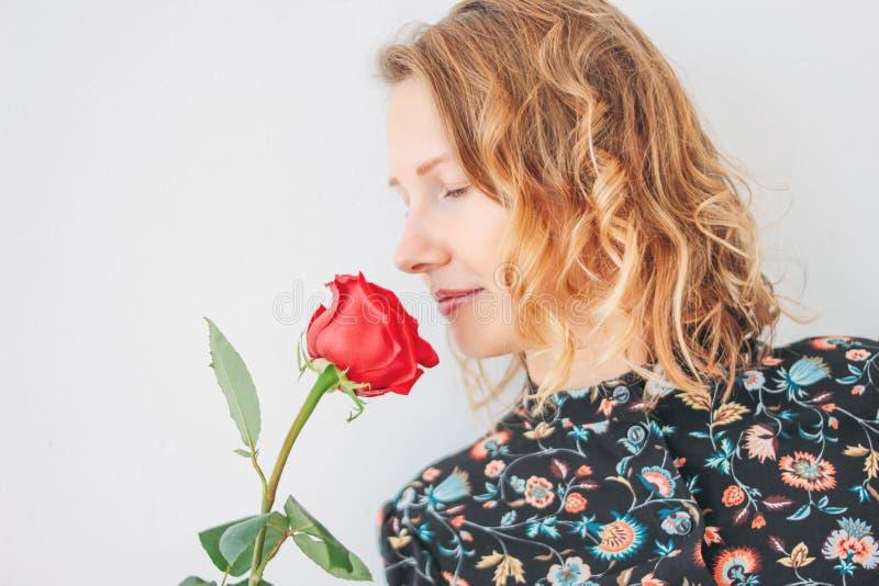 Belle jeune femme blonde romantique dans la robe avec la rose rouge sur le fond blanc d'isolement images stock