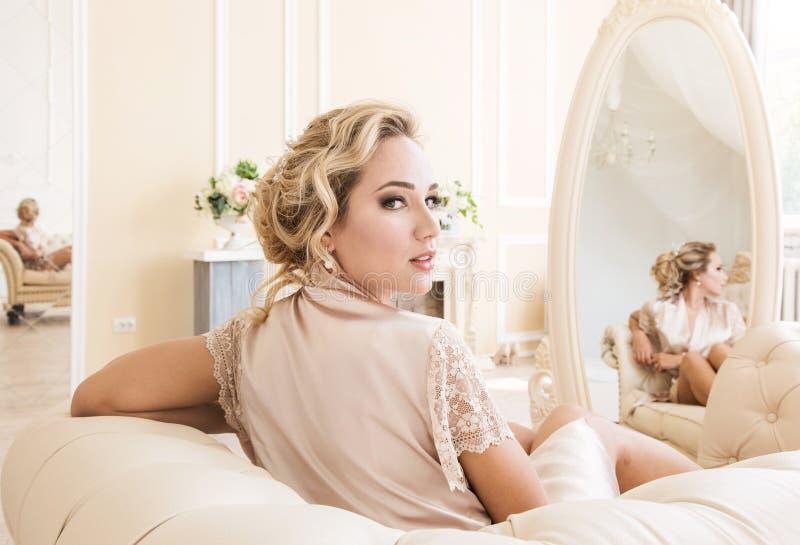 Belle jeune femme blonde sexy dans une robe longue en soie se reposant sur un sofa devant le miroir images stock