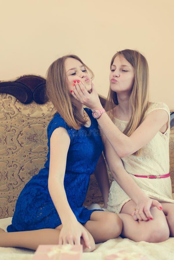 2 belle jeune femme blonde, soeurs ou meilleures jolies amies ayant l'amusement dans le lit se taquinant détente de sourire heure image libre de droits