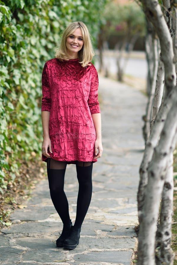 Belle jeune femme blonde souriant à l'arrière-plan urbain photographie stock libre de droits