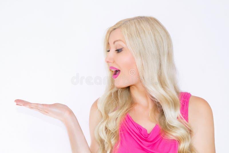 Belle jeune femme blonde souriant montrant un produit Belle fille indiquant le côté Présentation de votre produit photo libre de droits