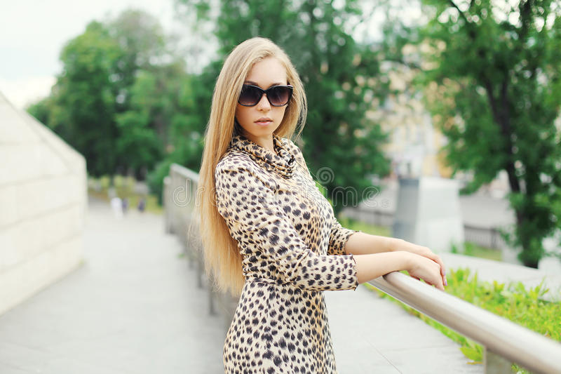 Belle jeune femme blonde utilisant une robe et des lunettes de soleil de léopard images stock