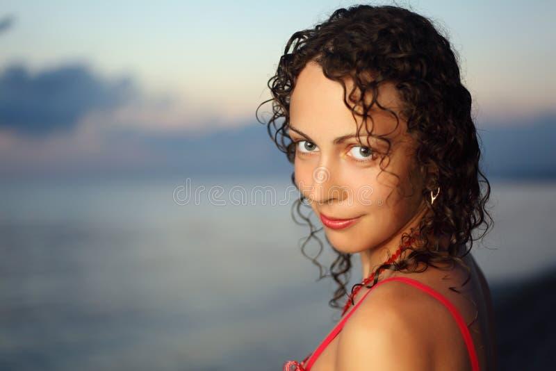 Belle jeune femme bouclée près de mer en soirée image libre de droits