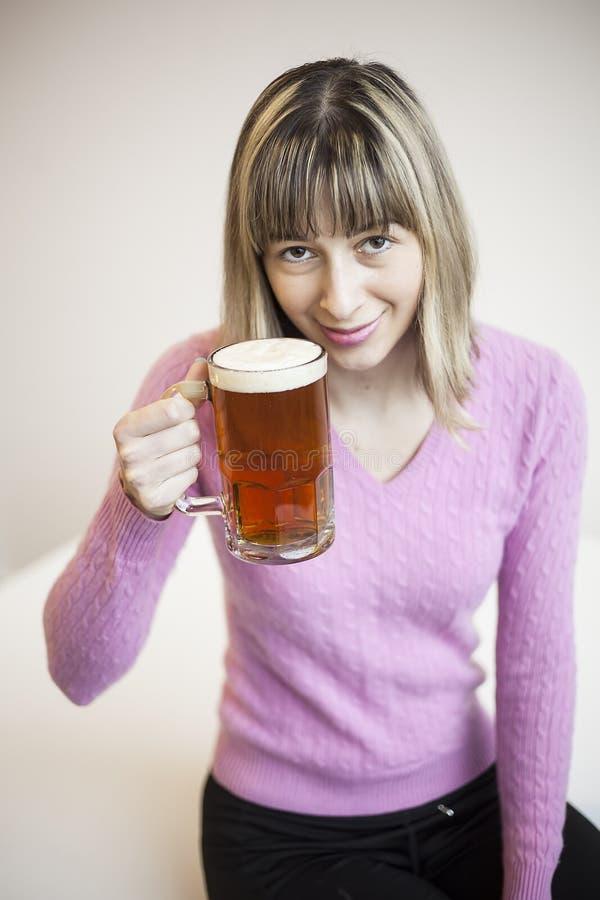 Tasse potable de jeune femme de bière photo stock