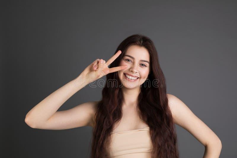 Belle jeune femme caucasienne au-dessus de fond souriant regardant la caméra image stock