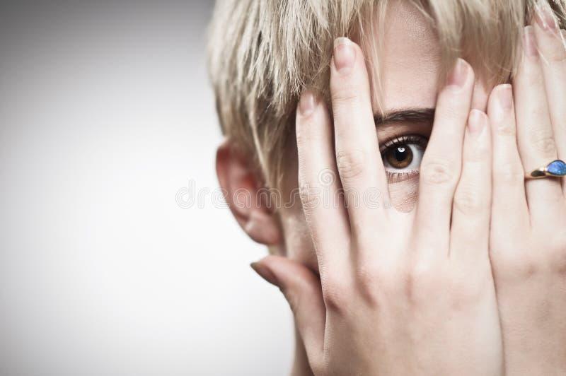 Belle jeune femme caucasienne jetant un coup d'oeil par des doigts photographie stock