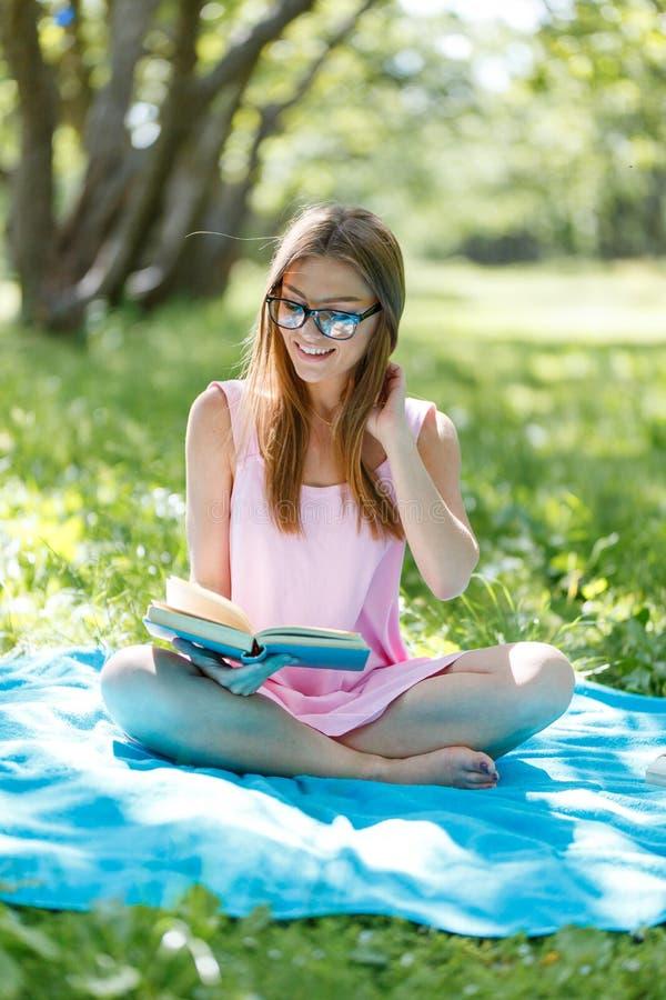 Belle jeune femme caucasienne lisant un livre extérieur Se reposer sur l'herbe images libres de droits