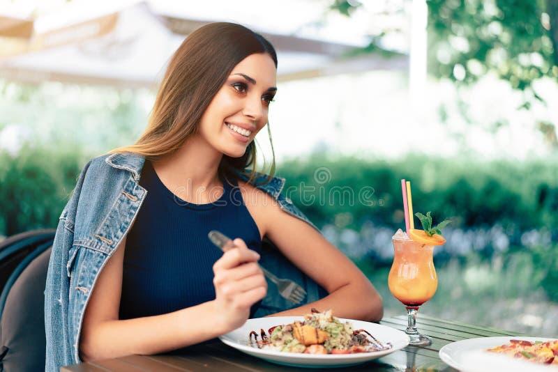 Belle jeune femme caucasienne mangeant de la salade de César fraîche dans un restaurant extérieur Humeur d'été, appréciant la nou images stock
