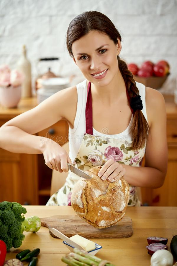 Belle jeune femme coupant en tranches le pain dans la cuisine à une table complètement des légumes organiques photo stock