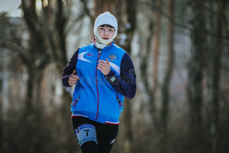 Belle jeune femme courant dans la forêt d'hiver photo libre de droits
