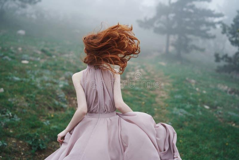 Belle jeune femme courant par la montagne dans une longue robe, nature photos libres de droits