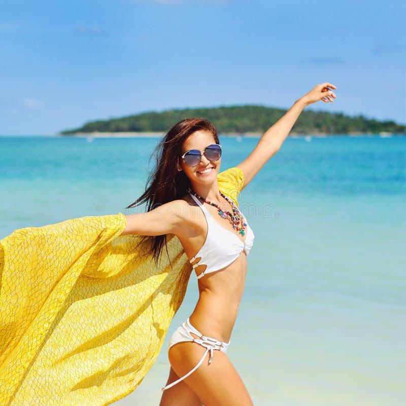 Belle jeune femme courant sur la plage avec un tissu jaune photographie stock libre de droits
