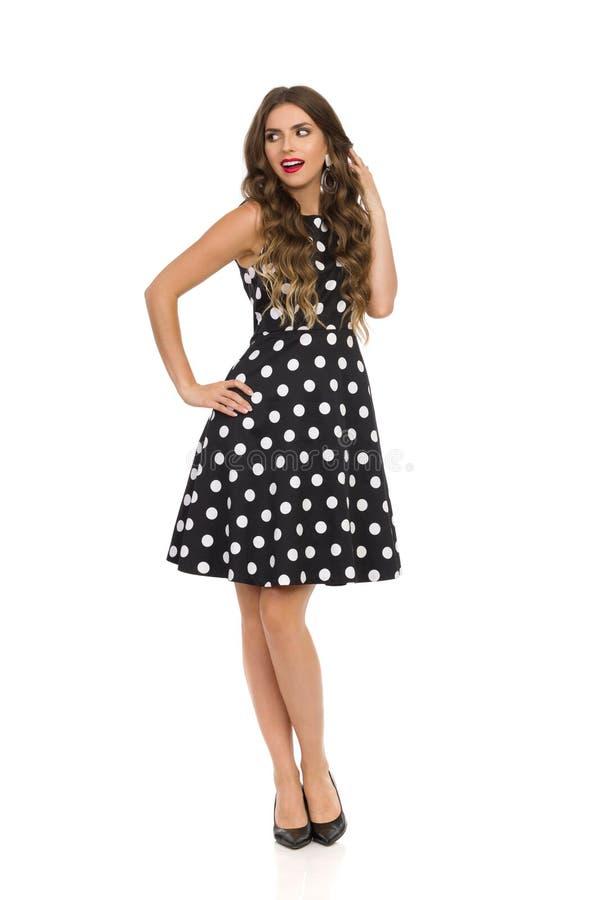 Belle jeune femme curieuse dans la robe de cocktail noire dans la polka Dots And High Heels Is regardant loin photos stock