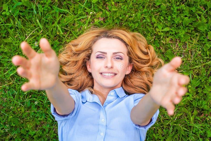 Belle jeune femme détendant dans l'herbe photo libre de droits