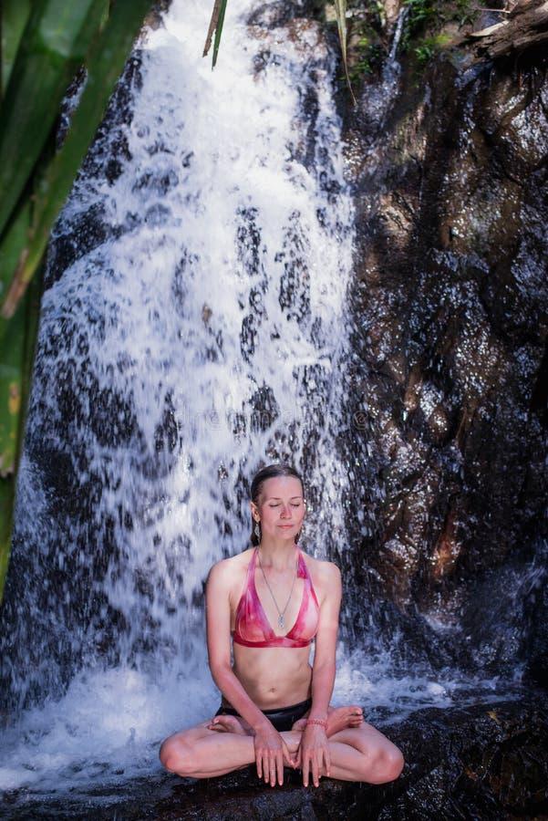 Belle jeune femme détendant sous la cascade à la forêt de jungle en nature photos libres de droits