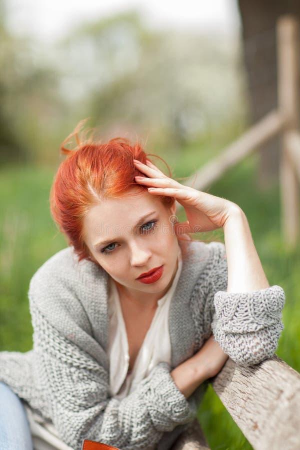 Belle jeune femme détendant sur un banc dehors dans l'environnement rural image libre de droits