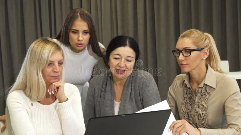 Belle jeune femme d'affaires à l'aide de l'ordinateur portable au cours de la réunion d'affaires avec des collègues photo stock