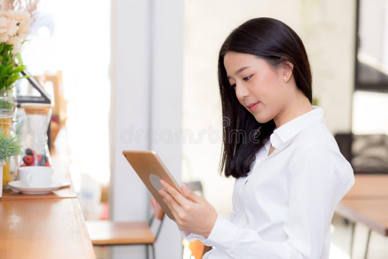 Belle jeune femme d'affaires asiatique tenant le comprimé, femme regardant le téléphone portable et travaillant le café d'Interne photographie stock