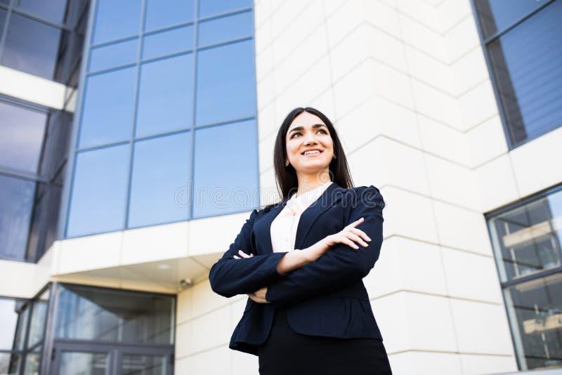 Belle jeune femme d'affaires contre les gratte-ciel du centre moderne d'affaires image libre de droits