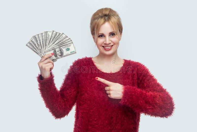 Belle jeune femme d'affaires gaie heureuse dans la position rouge de chemisier, tenant beaucoup de dollars, dirigeant le doigt et photographie stock