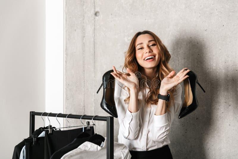 Belle jeune femme d'affaires habillée dans la chemise formelle de vêtements se tenant à l'intérieur près du cintre tenant des cha photo libre de droits