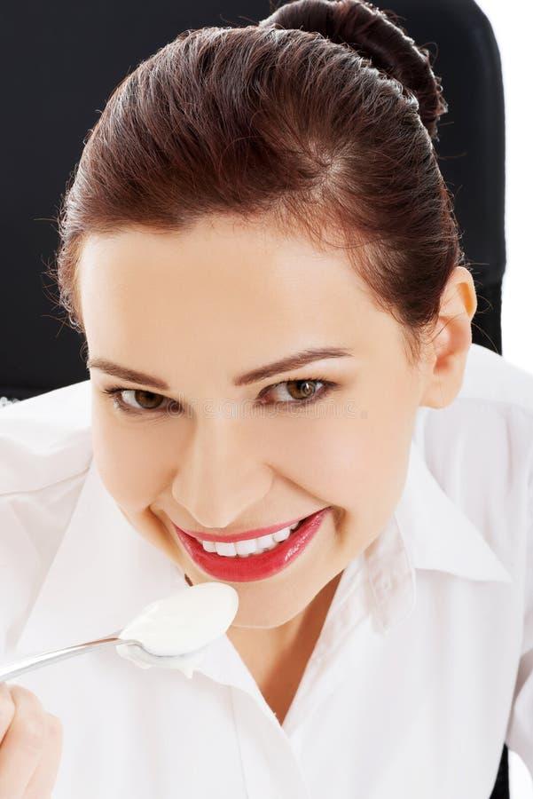 Belle jeune femme d'affaires mangeant du yaourt. images stock