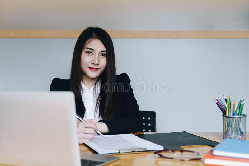 Belle jeune femme d'affaires s'asseyant au bureau devant l'ordinateur portable et travaillant sur le rapport de gestion photo libre de droits