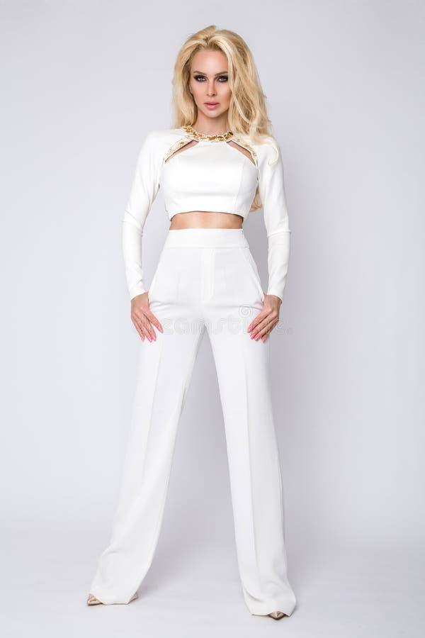 Belle jeune femme d'affaires sexy grande élégante de femme se tenant sur un fond blanc du pantalon et du chemisier blancs images libres de droits