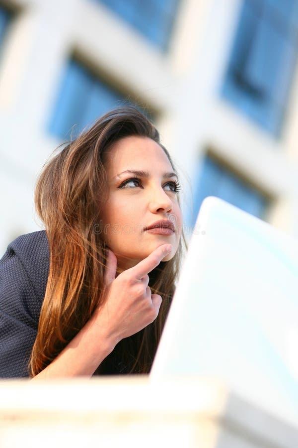 Belle jeune femme d'affaires sur penser d'ordinateur portatif images stock