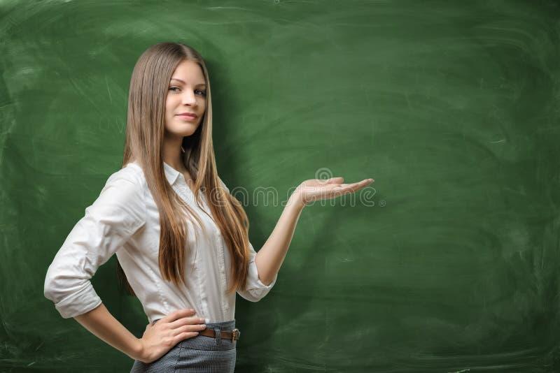 Belle jeune femme d'affaires tenant sa paume ouverte et montrant au secteur vide sur le tableau vert photographie stock