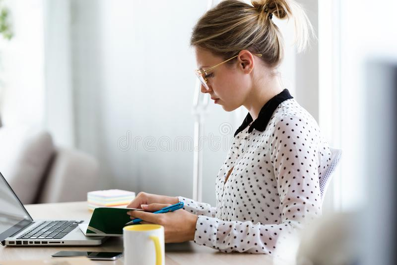 Belle jeune femme d'affaires travaillant avec son ordinateur portable et prenant des notes dans le bureau photo stock