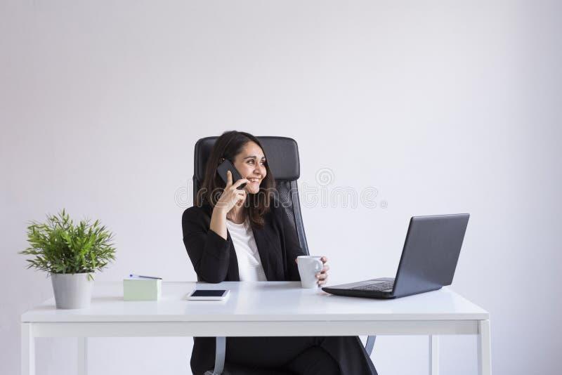 belle jeune femme d'affaires utilisant son ordinateur portable dans le bureau et parler à son téléphone portable Concept d'affair photo libre de droits