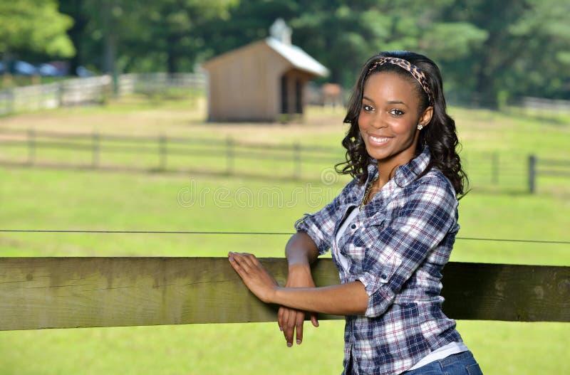 Belle jeune femme d'Afro-américain se tenant le long de la barrière de ferme - rurale photo stock