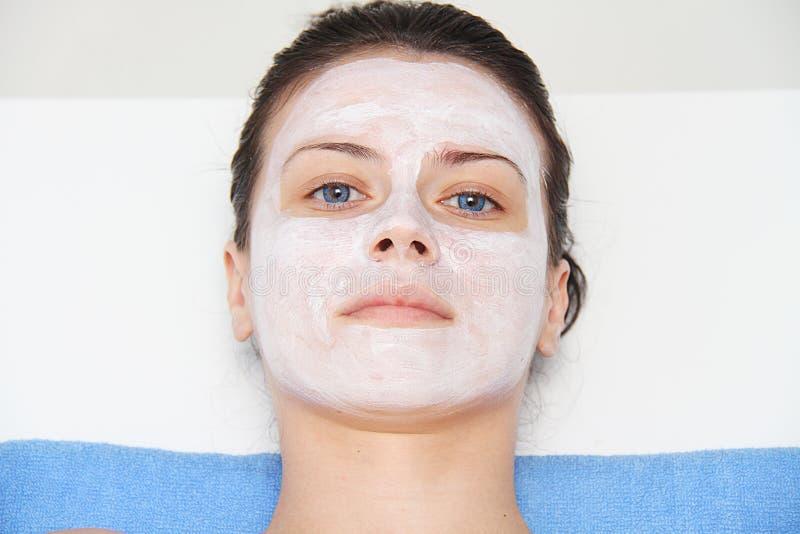 Belle jeune femme d'oeil bleu avec le masque de massage facial d'argile images stock