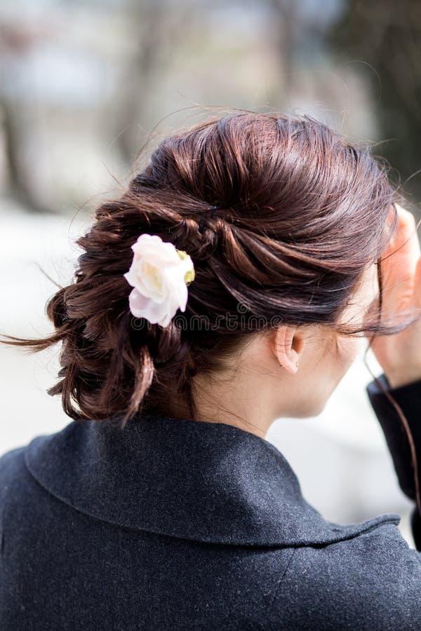Belle jeune femme d'une chevelure foncée avec la coiffure créative de tresse avec une fleur photos stock