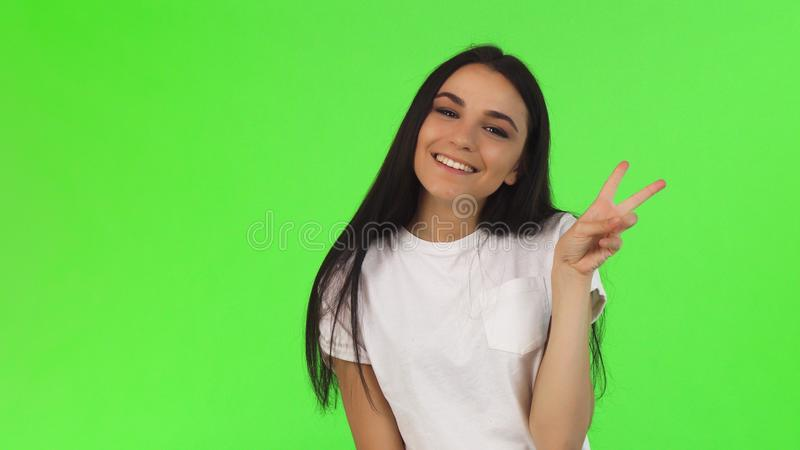Belle jeune femme d'une chevelure foncée souriant montrant le signe de paix images libres de droits