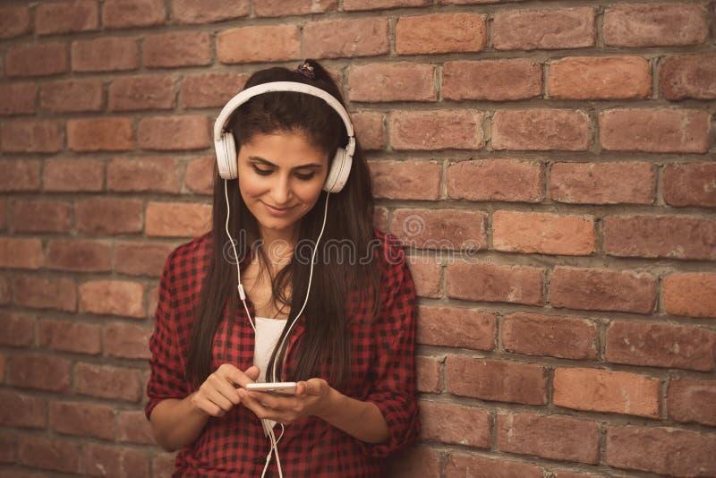 Belle jeune femme dans des écouteurs écoutant la musique sur le fond de brique photo stock