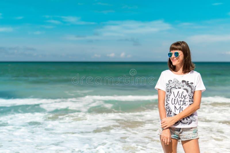 Belle jeune femme dans des lunettes de soleil posant sur la plage d'une île tropicale de Bali, Indonésie images libres de droits